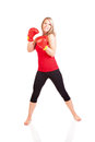 Portrait of pretty young woman doing boxing exercise beautiful in a red tanktop and gloves kickboxing Royalty Free Stock Photo