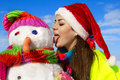 Portrait of a pretty young woman kissing a snowman Royalty Free Stock Photo
