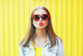 Portrait pretty young woman in red sunglasses blowing lips kiss over yellow