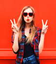 Portrait pretty young woman in red sunglasses shape of heart blowing lips making air kiss Royalty Free Stock Photo