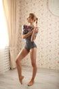 Portrait of a professional ballerina near window in sun light in home interior. Royalty Free Stock Photo