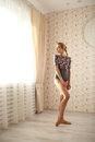 Portrait of a professional ballerina in sun light in home interior. Ballet concept. looking to window and smiling Royalty Free Stock Photo