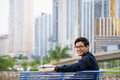 Portrait of proud and confident asian office worker chinese businessman sitting relaxing on bench in panama city with skyline Stock Images