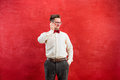 Portrait of puzzled man talking by phone a red background Royalty Free Stock Photo