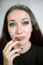 Portrait of a real female smoker young woman on light background in black t shirt with purple cigarette shallow depth field focus Royalty Free Stock Photos