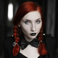 Photo : Portrait of red-haired girl in bow tie on a dark background, gothic style, girl with pigtails birch  outdoors