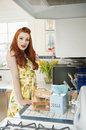 Portrait of a redheaded woman standing by the kitchen counter Royalty Free Stock Photo