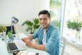 Portrait of a relaxed casual young asian business man with compu Royalty Free Stock Photo