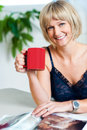 Portrait of a relaxed woman holding red coffee mug Royalty Free Stock Photos