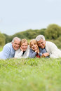 Portrait of retired seniors lying in grass smiling Royalty Free Stock Photo
