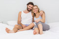 Portrait of romantic couple sitting on bed Royalty Free Stock Photo