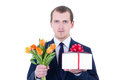 Portrait of romantic man holding gift box and flowers isolated o Stock Photo