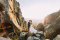 Portrait of romantic newlywed couple in yellow sunset lights on majestic mountain landscape with big rocks as backround Royalty Free Stock Photo