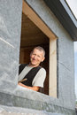 Portrait of a roofer looking by a dormer window through new Stock Photos