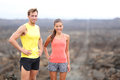 Portrait of runner couple resting after running trail cross county healthy lifestyle interracial fit caucasian Royalty Free Stock Images