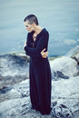 Portrait of sad beautiful Caucasian white young bald girl woman with shaved hair head standing by water lake looking away Royalty Free Stock Photo