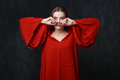 Portrait of a sad beautiful woman in red dress with wide sleeves wiping tears gray background Stock Photo