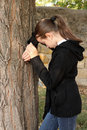 Portrait the sad girl near a tree. Royalty Free Stock Photo