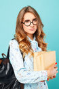 Portrait of a sad girl wearing glasses looking up over blue back Royalty Free Stock Photo
