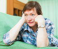 Portrait of sad senior woman having tough time and laying on couch Royalty Free Stock Photo