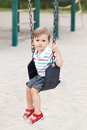 Portrait of sad upset worried little small boy toddler in tshirt and jeans shorts on swing on backyard playground outside Royalty Free Stock Photo