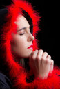 Portrait of sad woman in black cape praying with red feathered rim Royalty Free Stock Photos