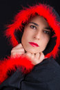 Portrait of sad woman in black cape and red fringe with feather Royalty Free Stock Photography