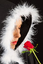 Portrait of sad woman in black cape and rose artistic conversion with red Stock Photo