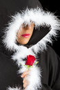 Portrait of sad woman in black cape and rose artistic conversion with red Stock Photography