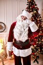 Portrait of Santa Claus with glasses near the fireplace and christmas tree with gifts. New year and Merry Christmas , happy Royalty Free Stock Photo