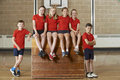 Portrait of school gym team sitting on vaulting horse Stock Image