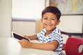 Portrait of schoolboy using digital tablet in classroom
