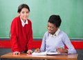 Portrait of schoolgirl with teacher reading binder cute little at desk in classroom Stock Photography