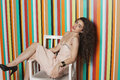 Portrait of a seductive young woman sitting on chair against colorful striped background Royalty Free Stock Image
