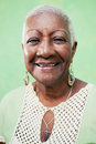 Portrait of senior black woman smiling at camera on green backgr