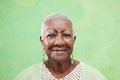 stock image of  Portrait of senior black woman smiling at camera on green backgr