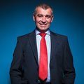 Portrait of a senior business man on blue studio background Royalty Free Stock Image