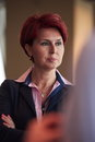 Portrait of senior business woman at office red hairstyle corporate interior Stock Photography