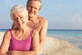 Portrait of senior couple on tropical beach holiday smiling to camera Stock Photography
