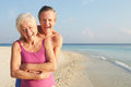 Portrait of senior couple on tropical beach holiday smiling to camera Stock Images