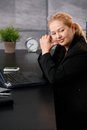 Portrait of senior executive businesswoman sitting at desk in office looking away Royalty Free Stock Photo