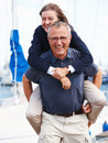 Portrait of senior man giving woman piggyback Stock Photography
