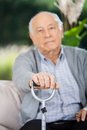 Portrait of senior man holding metal walking stick while sitting on couch at nursing home porch Stock Image