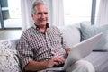 Portrait of senior man using laptop in living room Royalty Free Stock Photo