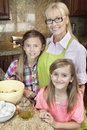 Portrait of a senior woman with granddaughters in kitchen women Stock Photography
