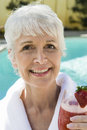 Portrait of senior woman holding strawberry cocktail closeup a smiling Royalty Free Stock Photo