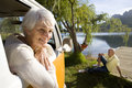 Portrait of senior woman leaning from window of camper van by lake senior man on jetty in background women men Royalty Free Stock Image