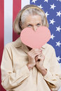 Portrait of senior woman with red paper heart against american flag Stock Photo