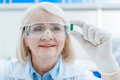 Portrait of senior woman scientist analyzing pill in hand Royalty Free Stock Photo