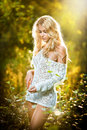 Portrait of a sensual young blonde female on field in sexy white short dress blouse Stock Photos